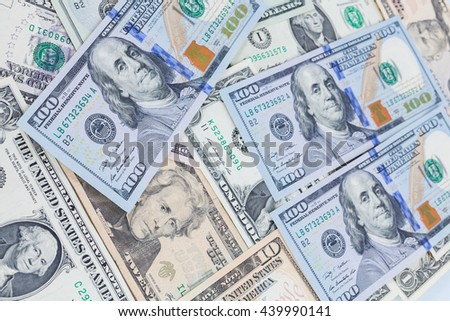 Multiple scattered American 100 dollar banknotes in full frame coverage with corner vignetting viewed from above in a conceptual financial background