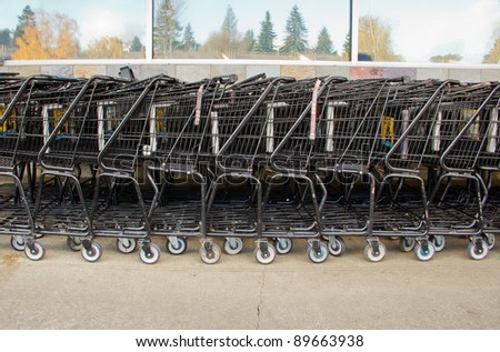 Multiple shopping carts stacked outside of grocery store - stock photo