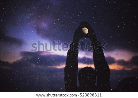 Multiple silhouette of a man holding a moon with stars
