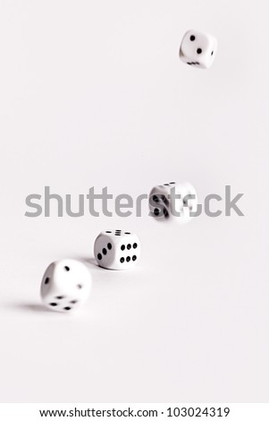 Multiple thrown dice bouncing across a white surface with movement and motion blur - stock photo