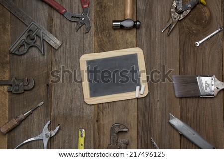 Multiple tools on wood Background surrounding chalkboard. - stock photo