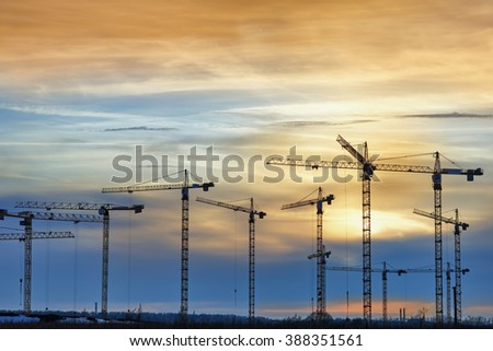 Multiple tower crane on a construction site at sunset - stock photo