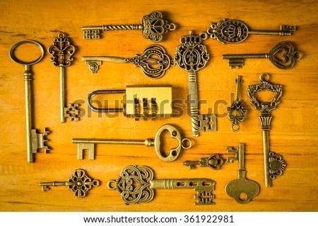Multiple vintage keys and ombination lock  on wood board. - stock photo