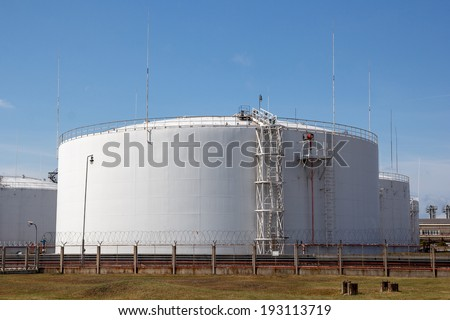 multiple white big oil storage tanks with a fence around them