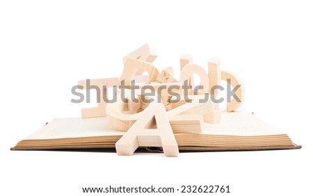 Multiple wooden letters over the opened book's surface, composition isolated over the white background - stock photo