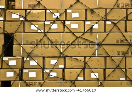 Multiple yellow cargo boxes with white address labels covered by secure netting abstract background. - stock photo
