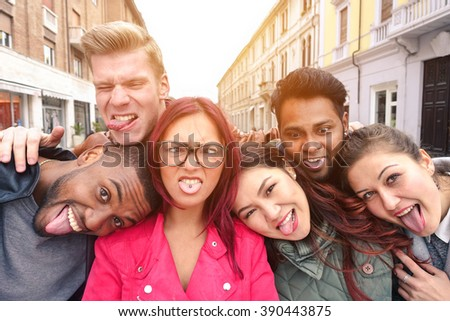 Multiracial best friends taking selfie outdoors in urban contest - Happy young people having fun together - Multi ethnic and Friendship concept - Soft vintage warm filtered look  - stock photo