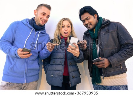 Multiracial best friends with smartphones looking surprised - Young students using phones online outdoors with white background  - Technology and friendship concept  - Soft warm filtered look - stock photo
