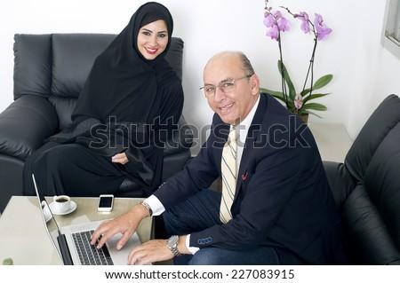 Multiracial Business meeting between a Senior Businessman & a woman wearing Hijab - stock photo