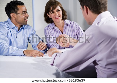 Multiracial business meeting in boardroom, shaking hands.  Shallow DOF, focus on handshake - stock photo