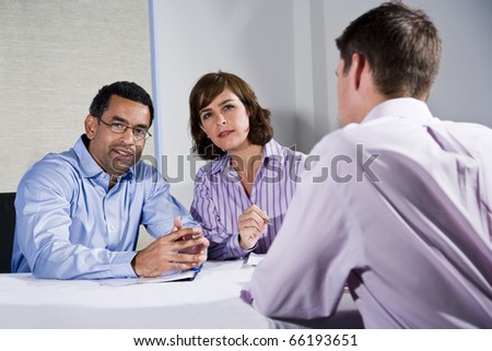 Multiracial business meeting in boardroom, sitting at a table, focus on people facing camera - stock photo