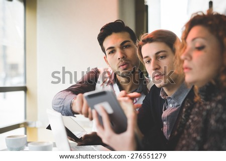 Multiracial business people working connected with technological devices at the bar indoor - stock photo