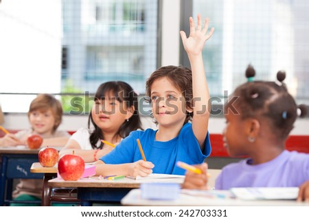 Multiracial classroom primary school. Kid raising his hand ready to answer.