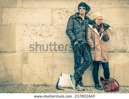Multiracial couple in love on a phase of mutual disinterest - Modern concept of connection in a relationship together with mobile phone technology - City urban lifestyle and everyday life rapport - stock photo