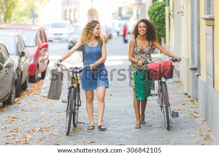 Multiracial couple riding bikes on the street. They are two women wearing summer clothes and walking on a small street with their bikes. They are bringing some shopping bags. Sun flare added. - stock photo