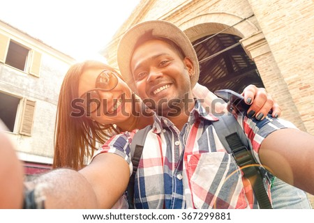 Multiracial couple taking selfie at old town trip - Fun concept with alternative fashion travelers - Indian boyfriend with caucasian girlfriend - Warm filter with powered sunlight and lens flare halo - stock photo