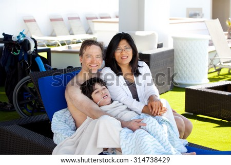 Multiracial couple with young disabled son on blue poolside lounger, drying off after swimming. Child has cerebral palsy.
