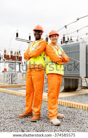 multiracial electrical co-workers in electric substation - stock photo