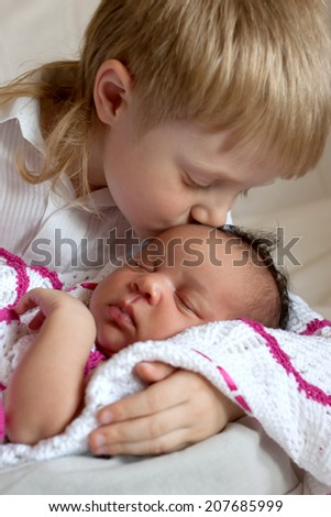 Multiracial family concept. Brother kissing newborn sister. - stock photo