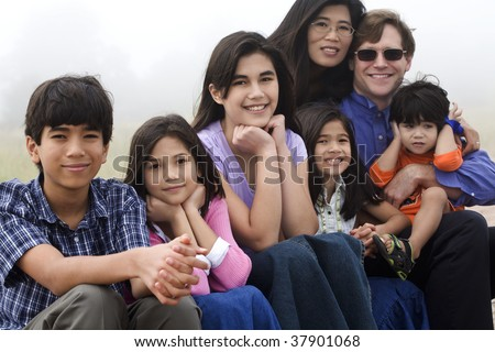 Multiracial family sitting on beach on misty, foggy day.