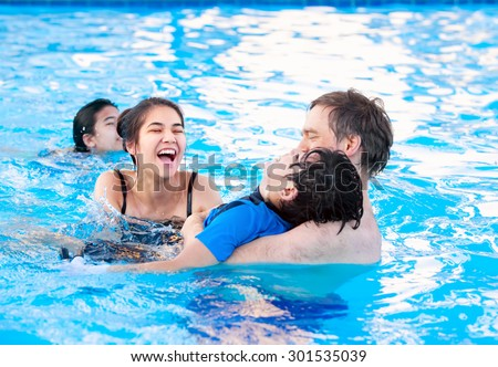 Multiracial family swimming together in pool. Disabled youngest son has cerebral palsy. - stock photo