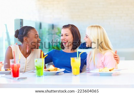 multiracial female friends enjoying meal in restaurant - stock photo