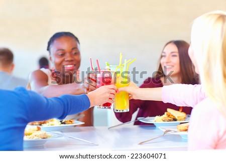 multiracial female friends having fun in restaurant - stock photo