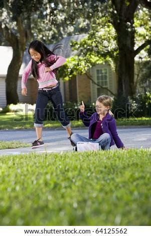 Multiracial friends having fun playing hopscotch on driveway - stock photo