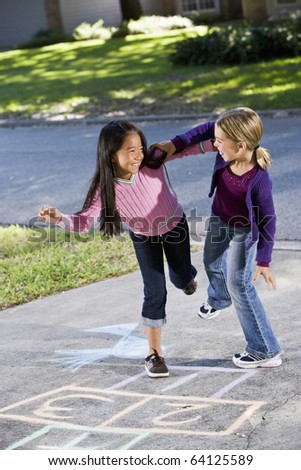 Multiracial friends having fun playing hopscotch on driveway - stock photo