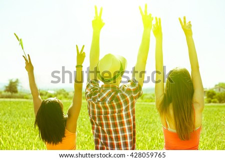 Multiracial friends putting hands up in countryside with back lighting - Multi ethnic young people enjoying sunny day outdoor - Freedom in nature concept - Focus on hat - Vintage old filter - stock photo