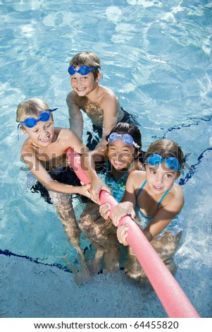 Multiracial friends tugging on pool toy in swimming pool, ages 7 to 9 - stock photo