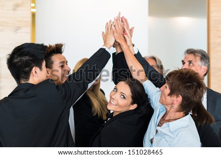 Multiracial group of eight diverse businesspeople standing in a circle joining hands in a team with office scenario as background. Frontmost attractive businesswoman is looking towards camera smiling. - stock photo