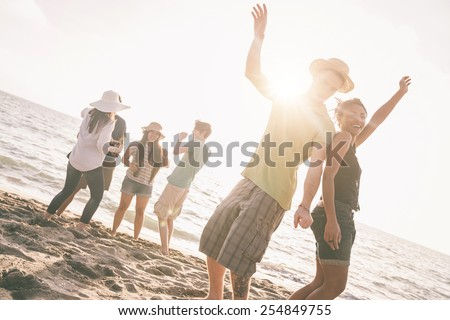 Multiracial group of friends having a party at beach. There are asiatic, black and caucasian persons. Friendship, immigration, integration concepts. Also refers to summer and party. - stock photo