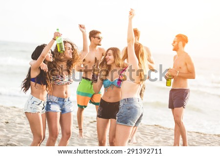 Multiracial group of friends having a party on the beach, dancing and drinking beer. They are teenagers, four girls and three boys, standing just next to the seaside. - stock photo