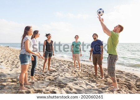 Multiracial Group of Friends Playing Volleyball at Beach