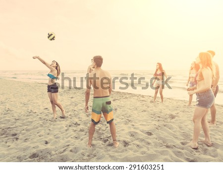 Multiracial group of friends playing with ball on the beach. There are four girls and three boys, with a filipina girl and a spanish boy.