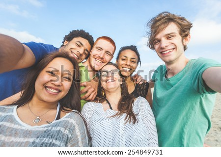 Multiracial group of friends taking selfie at beach. One girl is asiatic, two persons are black and three are caucasian. Friendship, immigration, integration and summer concepts. - stock photo