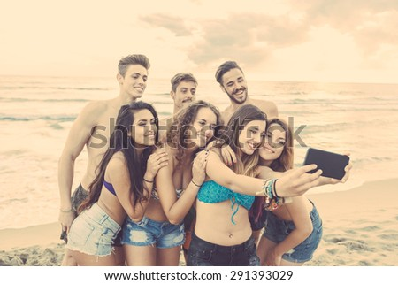 Multiracial group of friends taking selfie on the beach. They are teenagers, four girls and three boys, standing just next to the seaside. - stock photo