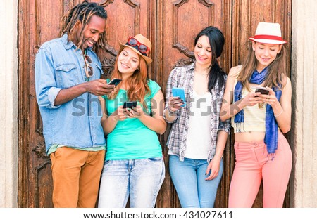 Multiracial group of friends texting sms and looking down to cell phone - Multicultural row of students using mobile - Concept of teens addiction to web social network technology - Soft vintage filter - stock photo