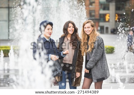 Multiracial group of girls having fun in London in a public square with fountains on the ground. The group consists of three girls, one is from Korea, one from Spain and one from Holland - stock photo