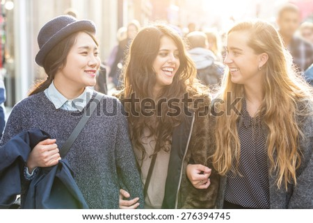Multiracial group of girls walking in London. Urban background with busy road and sidewalk, friendship and lifestyle concepts.Group consists of one girl from Korea, one from Spain and one from Holland - stock photo