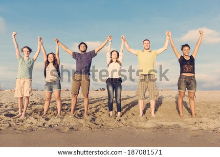 Multiracial Group of People with Raised Arms looking at Sunset - stock photo