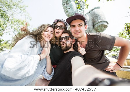 Multiracial group of young hipster friends make selfie photo with smartphone camera in Bali while traveling in Asia on vacation. Funny outdoor activity of young students away from home.  - stock photo