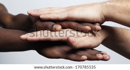 Multiracial hands together forming a pile over gray background - stock photo