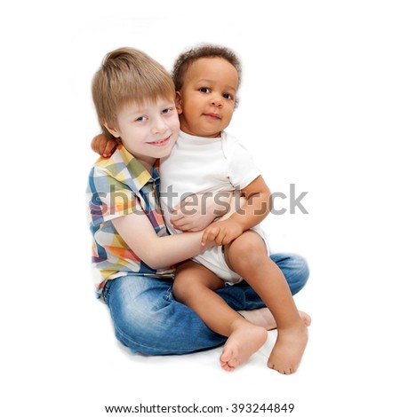 Multiracial happy family. White brother hugging black baby sister.