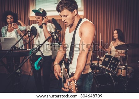 Multiracial music band performing in a recording studio  - stock photo
