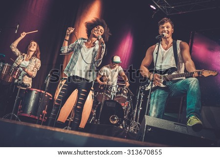 Multiracial music band performing on a stage  - stock photo