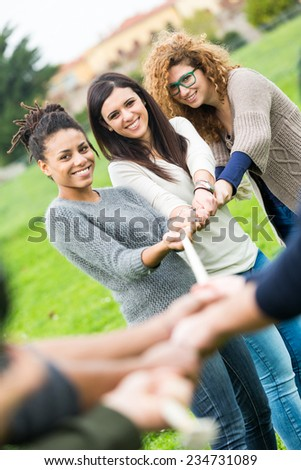 Multiracial People Playing Tug of War. Three Women playing against Three Men and Looking at them - stock photo