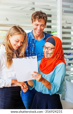 Multiracial team working together on documents - stock photo
