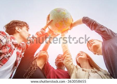 Multiracial Teen Couple Holding Globe Map - stock - stock photo
